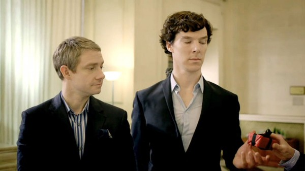 Martin Freeman as John Watson standing next to Benedict Cumberbatch as Sherlock Holmes looking pleased as Sherlock looks skeptically at a small, square, gift wrapped box being handed to him