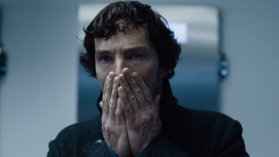 Benedict Cumberbatch as Sherlock Holmes looking shocked and horrified with hands covering mouth and nose