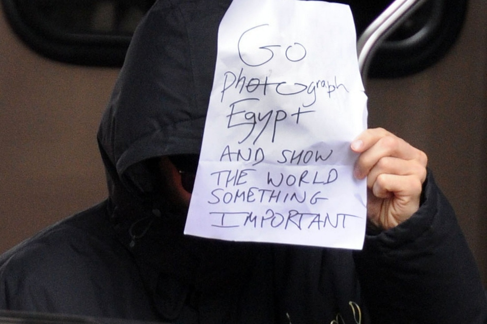Benedict Cumberbatch in black hoodie and sunglasses holds a sign in front of his face