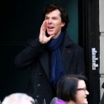 Benedict Cumberbatch as BBC Sherlock in coat yelling from the entrance of Baker Street flat.