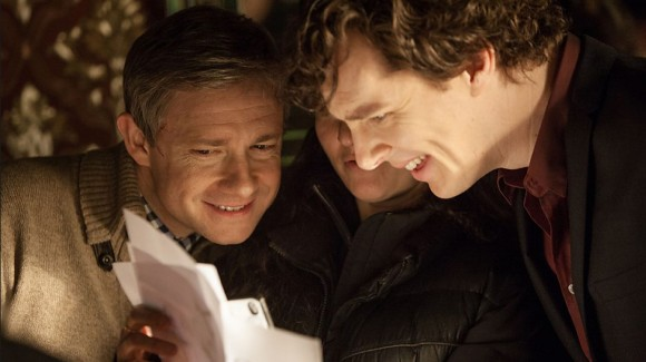 Martin Freeman as John Watson and Benedict Cumberbatch as BBC Sherlock Holmes reading pages over someone's shoulder.